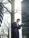 Businessman Reading Newspaper Under Tree royalty free stock photos