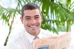 Businessman reading a newspaper in workplace Royalty Free Stock Image