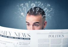 Businessman reading newspaper. Young confused businessman reading daily newspaper with question marks above his head Royalty Free Stock Image