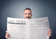 Businessman reading newspaper. Young smart businessman reading daily newspaper Royalty Free Stock Photo