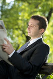 Businessman reading newspapers outdoors Royalty Free Stock Image