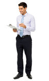 Businessman Reading Notes On Clipboard. Full length of smiling businessman reading notes on clipboard against white background. Vertical shot Royalty Free Stock Image
