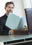 Businessman Reading Notes In File At Desk Stock Photos