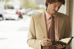 Businessman Reading Notes In Organizer Stock Photo