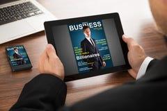 Businessman reading online magazine Stock Image