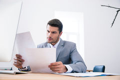 Businessman reading papers in office royalty free stock photography