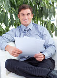 Businessman reading papers and smiling Royalty Free Stock Photography