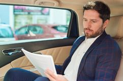 Businessman reading paperwork while being driven through the city. Focused young businessman sitting in the backseat of a car driving through the city reading Royalty Free Stock Images