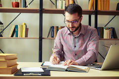 Businessman reading paperwork and taking notes Royalty Free Stock Photography