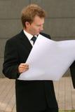 Businessman reading plans Stock Image