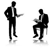 Businessman reading report silhouettes Stock Photo