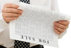 Businessman reading sales ads. Closeup on hands and lorem ipsum paper stock photography
