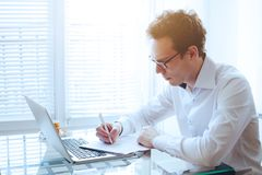 Businessman reading and signing contract or documents. Businessman reading and signing contract in modern bright office Stock Images
