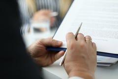 Businessman reading text of agreement stock photos