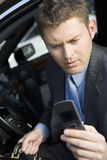 Businessman Reading Text Message On His Cell Phone Royalty Free Stock Photos