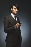 Businessman reading text message on his smart phone. Handsome young businessman reading text message on his smart phone. Mixed race male model in business suit Stock Images