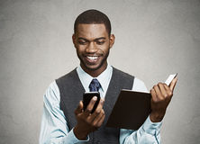 Businessman reading text message on mobile holding book simultan Royalty Free Stock Photography