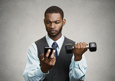 Businessman reading text message on mobile lifting weight simult Royalty Free Stock Photos