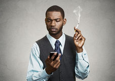 Businessman reading text messsage on his smartphone, smoking cig Royalty Free Stock Images