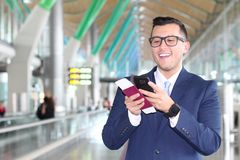 Businessman reading an update on his cellphone at the airport Stock Photos