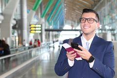 Businessman reading an update on his cellphone at the airport Royalty Free Stock Photography