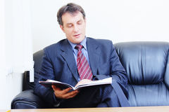 Businessman reads magazine Stock Images