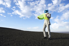 Businessman Reads Map on Flexible Display Tablet. Explorer businessman in lunar landscape reads electronic map on future technology flexible display tablet stock image