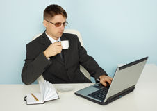 Businessman reads news online and drinking coffee Royalty Free Stock Image