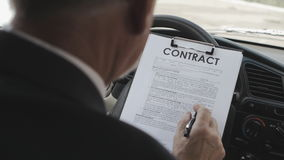 Businessman reads and signs a contract while sitting in the car. stock video footage