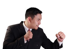 Businessman Ready To Fight. Business concept image of an Asian businessman ready to fight with his punch on white stock photography