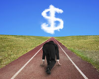 Businessman ready to race on running track toward dollar sign. Businessman ready to race on running track toward white dollar sign shape cloud, with blue sky stock photography