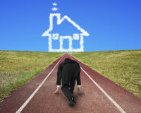 Businessman ready to race on running track toward house clouds. Businessman ready to race on running track toward house shape clouds, with blue sky background royalty free stock photography