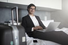 Businessman ready to travel works with his laptop. Businessman at home ready to travel works with his laptop royalty free stock photography