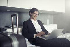 Businessman ready to travel works with his laptop. Businessman at home ready to travel works with his laptop stock images