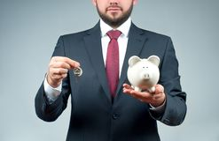 Businessman or real estate agent is holding piggy bank and keys. Royalty Free Stock Photo