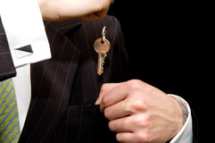 Businessman - real estate concept. Real estate concept, Man saving his new department key into his pocket Stock Image