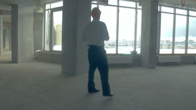 Businessman, realtor, investor in hard hat walking in unfinished building. Skyscraper inside under Construction. 4K stock footage