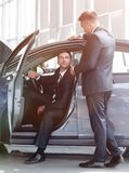 Businessman receives from the Manager the keys,sitting behind the wheel of a new car. Lifestyle stock photos