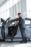 Businessman receives from the Manager the keys,sitting behind the wheel of a new car. Lifestyle stock photography
