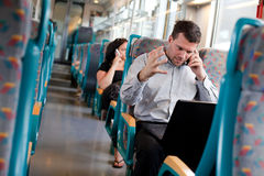 Businessman receiving bad news on a train Stock Image