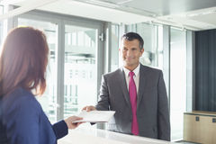 Businessman receiving document from receptionist in office Stock Images