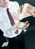 Businessman receiving money. Isolated on black background stock images