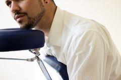 Businessman receiving shiatsu on a  massage chair. Businessman receiving shiatsu on a quick massage chair Stock Photo