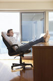 Businessman Reclining With Feet Up On Desk Stock Image