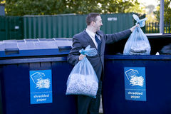 A businessman recycling bags of shredded paper Stock Photo