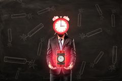 Businessman with red alarm clock instead of head holding big red dynamite time bomb on black background. Businessman and management. Financial risks. Business stock photo