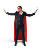 Businessman in a red cape and a red eye mask with hands raised as to stop something on his sides on white background. Stock Image