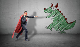 A businessman in a red cape standing in fighting pose ready to fight a picture of a dragon on the nearest wall. Stock Photo