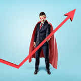 A businessman in a red flowing cape trying to keep the upward looking red arrow with his hand. Stock Image