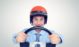 Businessman in a red helmet with steering wheel. Car drive concept Stock Image